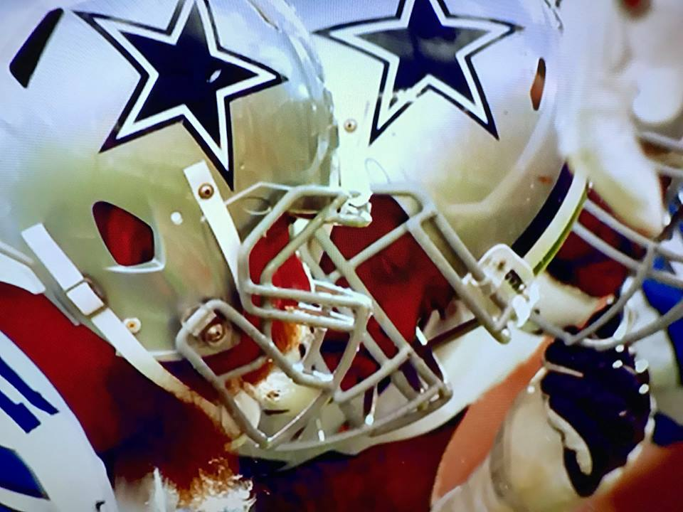 Close-up picture/screenshot of Dallas Cowboys players in huddle/on the line
