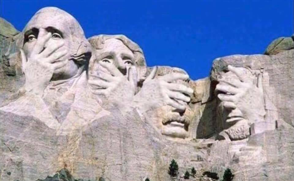 Photograph of Mount Rushmore with hands over faces