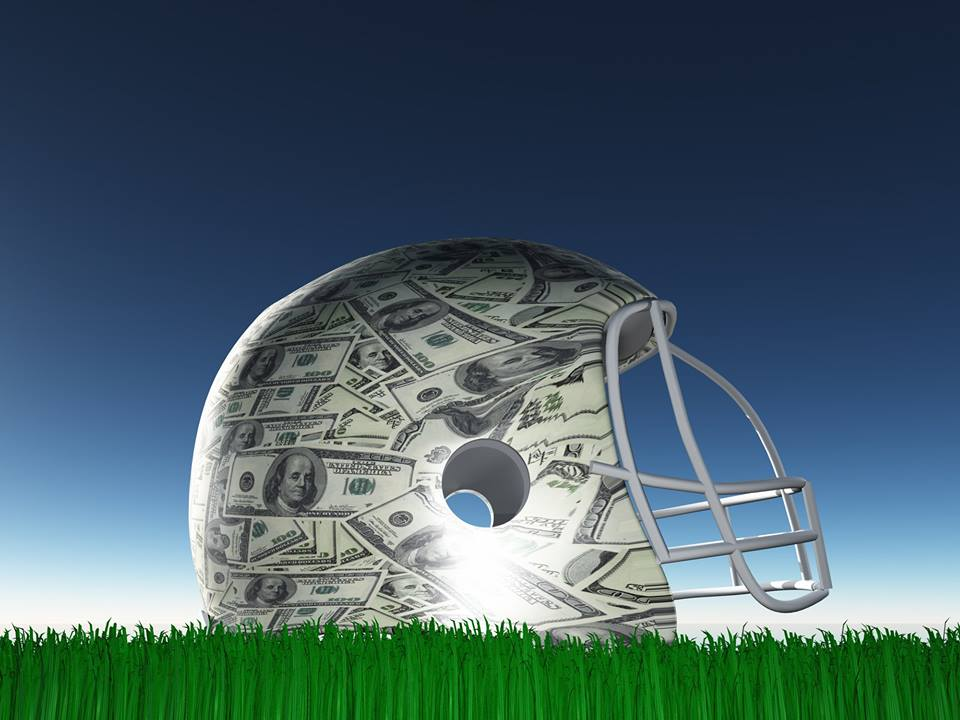 Photograph of football helmet with 100 dollar bills