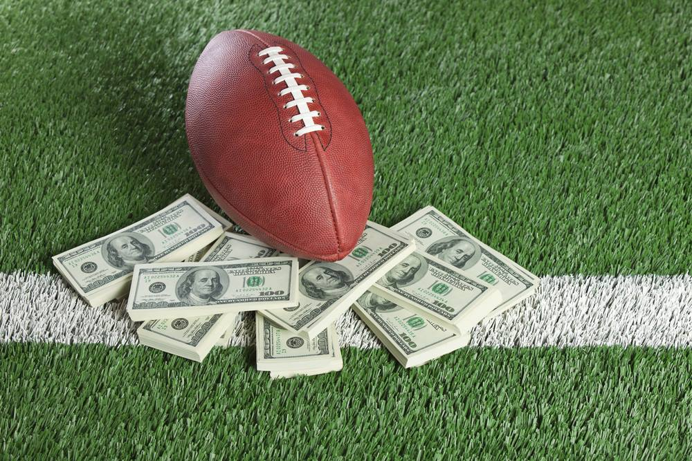 Photograph of football with stacks of 100 dollar bills