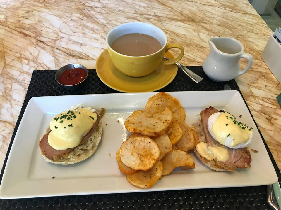 Picture of breakfast (eggs Benedict, hash browns, coffee, ketchup)
