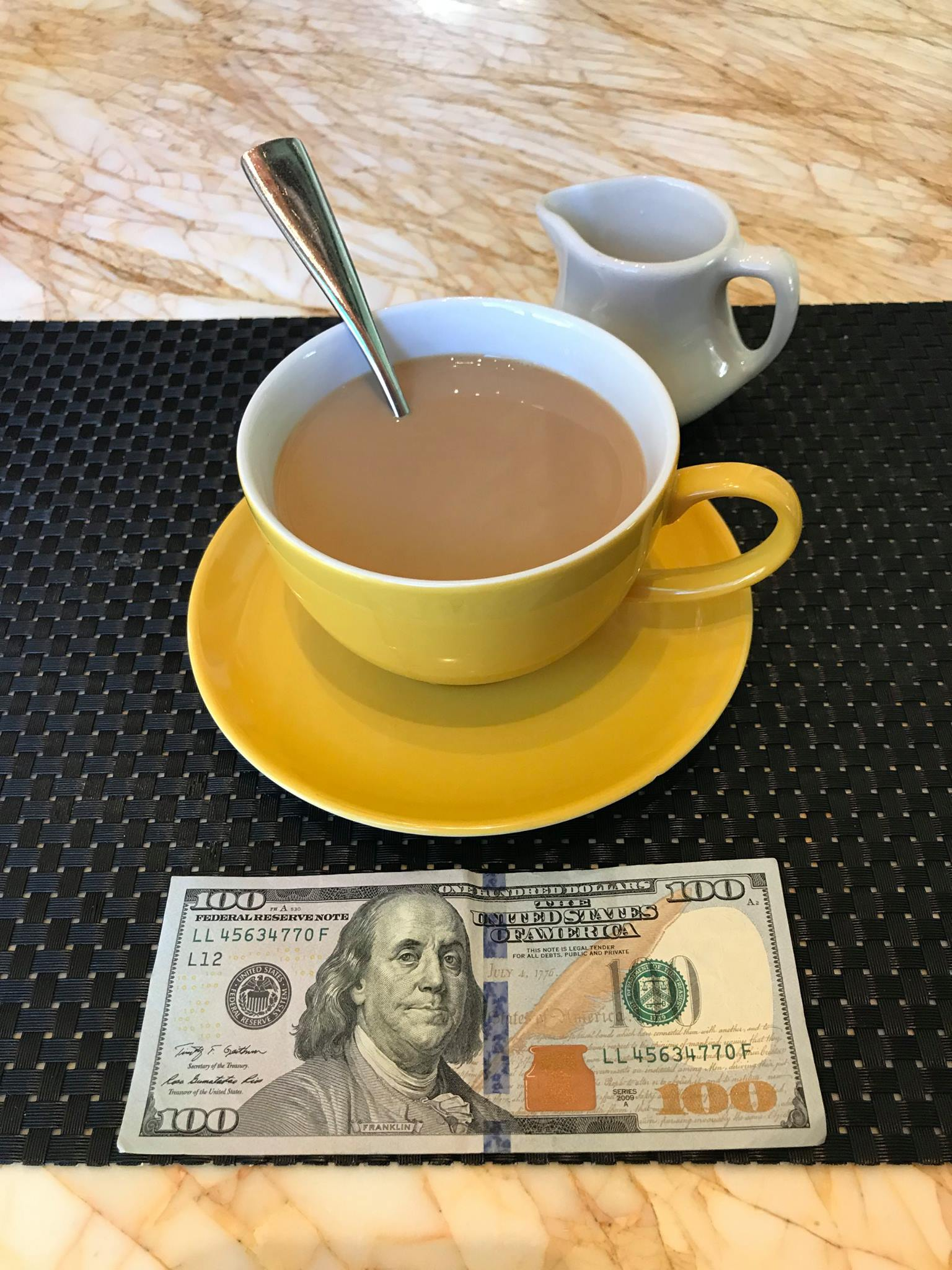 Picture of coffee-filled cup and saucer (yellow) with $100 bill facing up