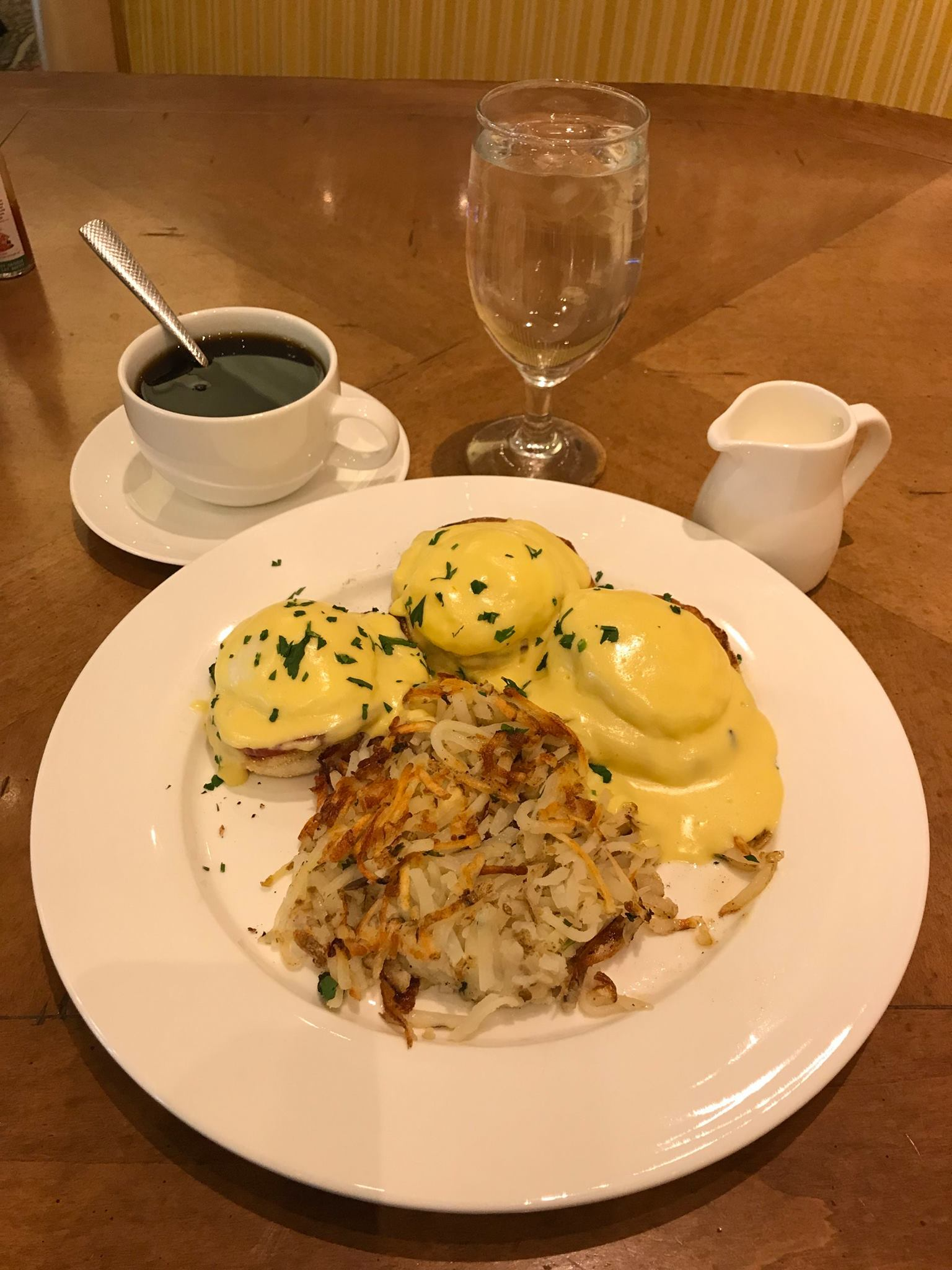 Picture of eggs Benedict, hash browns, and coffee