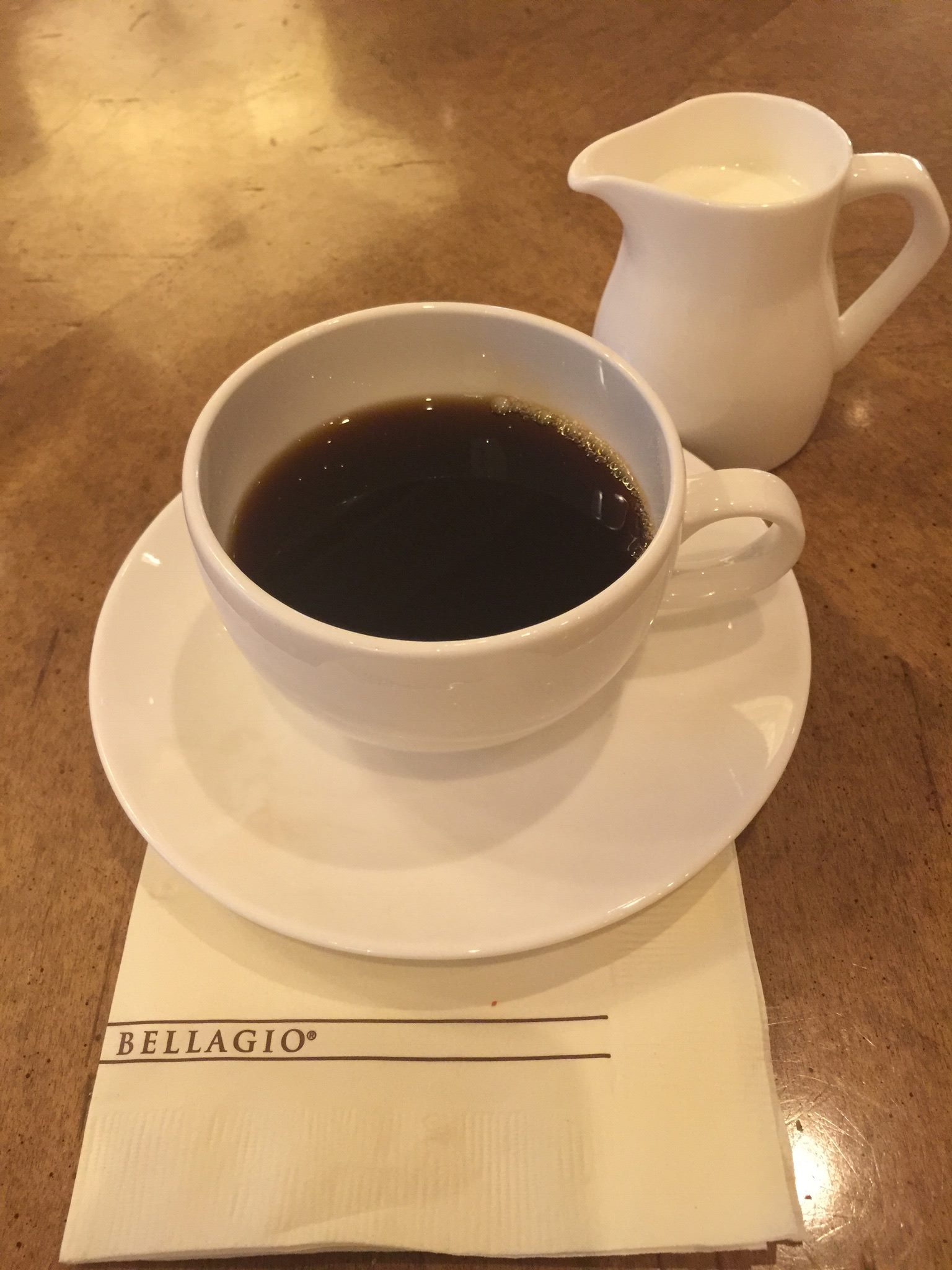 Picture of coffee-filled cup and saucer on top of Bellagio napkin